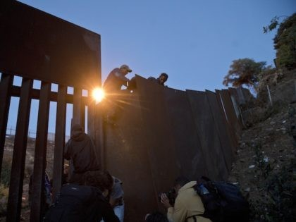 A Honduran migrant helps other immigrants cross to the U.S. side of the border wall, in Tijuana, Mexico, Sunday, Dec. 2, 2018. Thousands of migrants who traveled via caravan are seeking asylum in the U.S., but face a decision between waiting months or crossing illegally, because the U.S. government only …