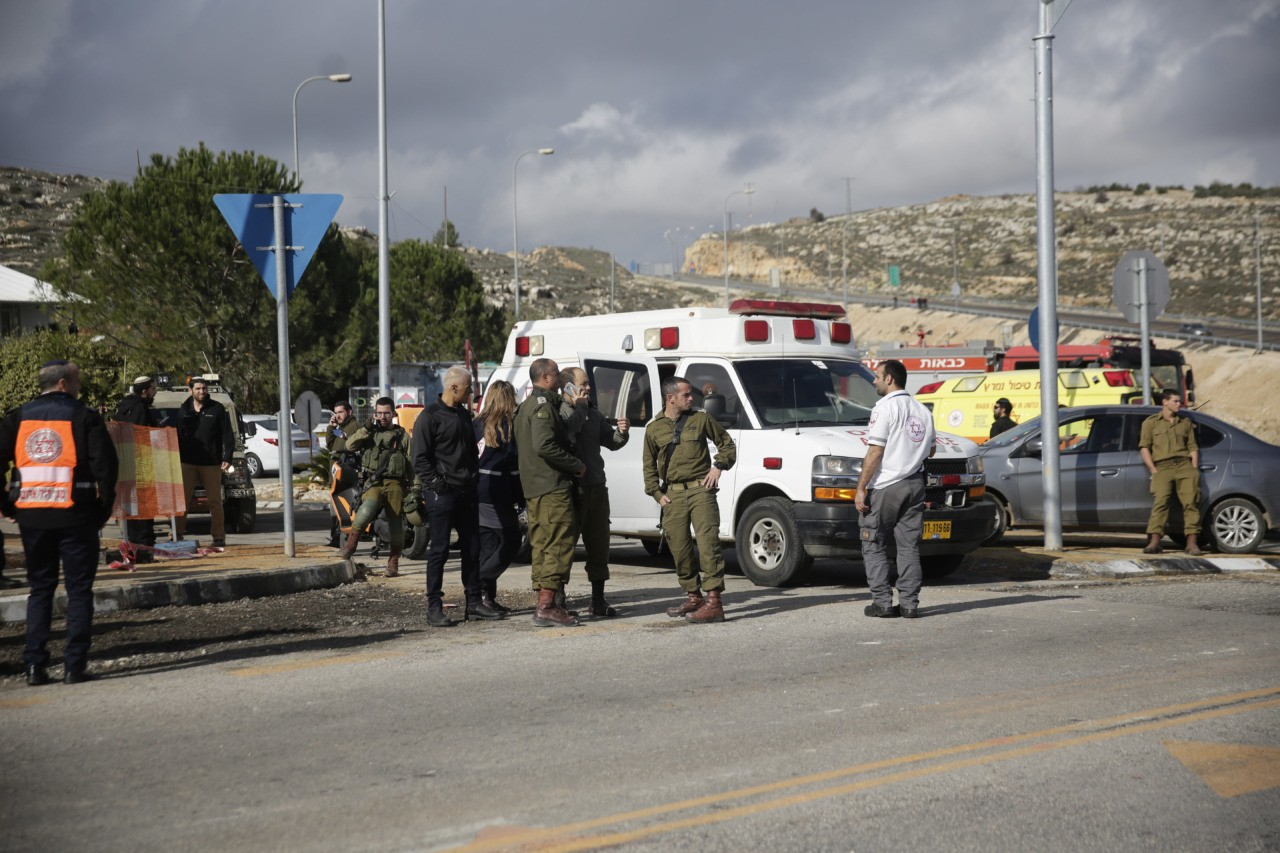 Israeli soldiers stand at the scene of an attack near the settlement of Givat Assaf in the West Bank, Thursday, Dec. 13, 2018. A Palestinian gunman opened fire at a bus stop outside a West Bank settlement on Thursday, shooting at soldiers and civilians and killing at least two Israelis before fleeing, the military and Israel's rescue service said. (AP Photo/Mahmoud Illean)