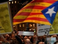 People hold placards reading 'We won´t give up' and a Catalan pro-independence 'estelada' during a demonstration in Barcelona on October 16, 2018, marking the one year anniversary of the detention of two grass-root Catalan separatist leaders, Jordi Sanchez and Jordi Cuixart. (Photo by LLUIS GENE / AFP) (Photo credit should …