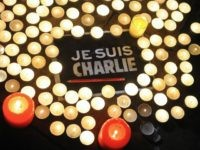Candles are placed next to a sign reading 'Je suis Charlie' (I am Charlie) and a pen in La Rochelle on January 7, 2015, as people gathered to pay tribute to the twelve people killed in an attack by two armed gunmen on the offices of French satirical newspaper Charlie …