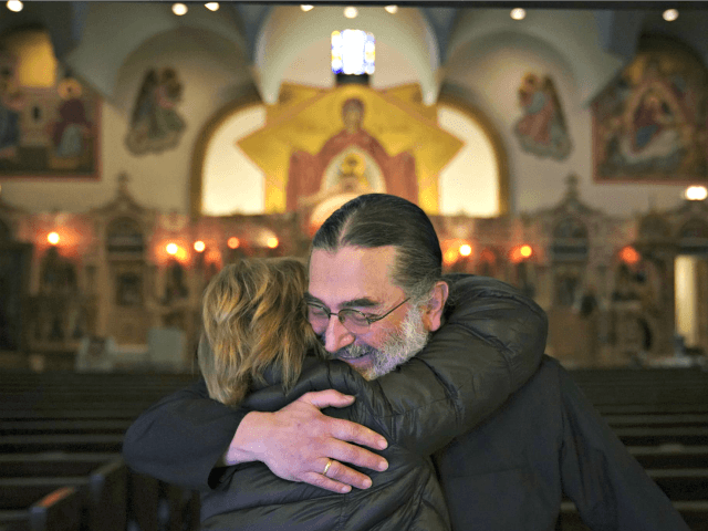 "Rev. Nicholas Jonas hugs a longtime parishioner of Holy Trinity Greek Orthodox Church, which avoided being sold at auction, Friday, Dec. 14, 2018, in Chicago. The 120-year-old Chicago church was saved from auction after a midnight call from a group of donors, which one church official said was ""a Christmas …"