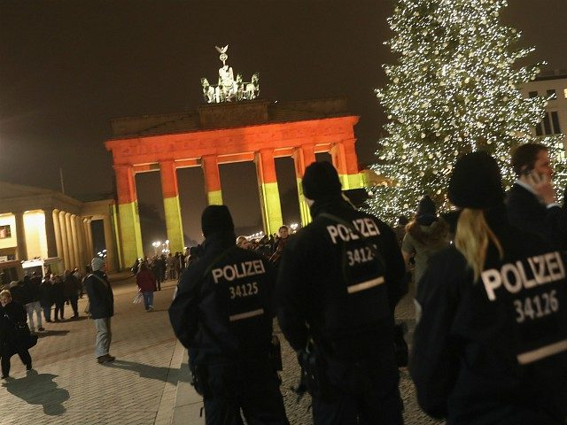 BERLIN, GERMANY - DECEMBER 20: The Brandenburg Gate stands illuminated in the colors of the German flag as police walk past the day after a truck drove into a crowded Christmas market in the city center on December 20, 2016 in Berlin, Germany. So far 12 people are confirmed dead …