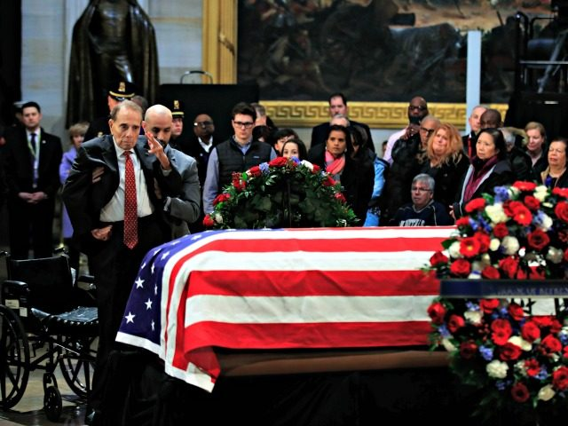 Former Sen. Bob Dole salutes the flag-draped casket containing the remains of former President George H.W. Bush as he lies in state at the U.S. Capitol in Washington Tuesday Dec. 4 2018