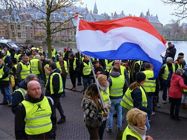 Dutch police lead a small group of yellow jacket protesters away from the Dutch Parliament in The Hague, Netherlands, on Saturday, Dec. 1, 2018. Police closed off the parliamentary complex after about 100 demonstrators gathered outside protesting government policy as the yellow vest movement spread into the Netherlands. (AP Photo/Mike …