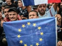A migrant holds an European Union flag as migrants and refugees stage a demonstration at Istanbul's Esenler Bus Terminal on September 19, 2015 after authorities withheld tickets to Turkish border towns. Hundreds of refugees camped out at the main bus station in Istanbul for a fifth night running after being …