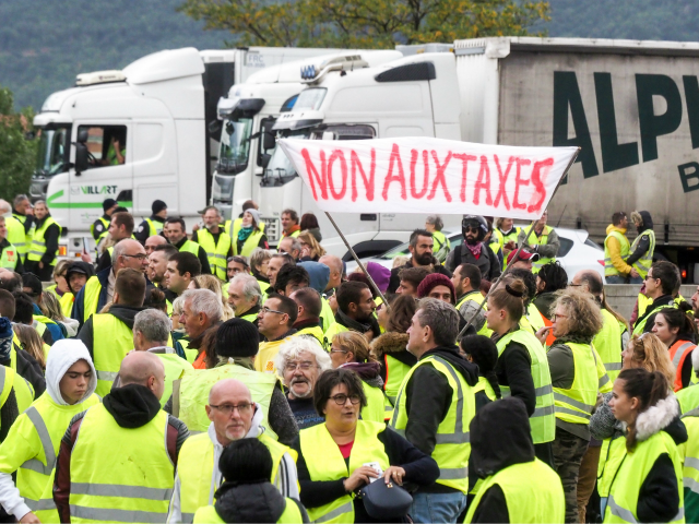 Demonstrators wearing Yellow Vests (Gilets jaunes) hold banner as they block the traffic during a protest against the rising of the fuel and oil prices on November 17, 2018 in Le Boulou near the border with Spain. - Thousands of drivers blocked roads across France on November 17 in a …