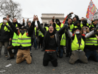 PARIS, FRANCE - DECEMBER 08: Demonstrators kneel and gesture with victory signs as they take part in the demonstration of the yellow vests at the Arc de Triomphe on December 08, 2018 in Paris France. ''Yellow Vests' ('Gilet Jaunes' or 'Vestes Jaunes') is a protest movement without political affiliation which …