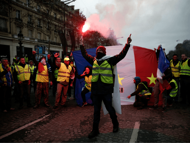 Protestors wearing 'yellow vests' (gilets jaunes) wave a French flag as they demonstrate against rising costs of living in the Champs Elysees in Paris on December 8, 2018. - Paris was on high alert on December 8 with major security measures in place ahead of fresh 'yellow vest' protests which …