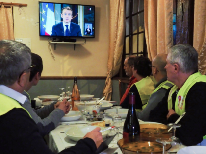 Yellow vest (gilets jaunes) protestors take notes as thet watch French President Emmanuel Macron's speech on TV on December 10, 2018 at a restaurant with French deputy Richard Damos, in Fay-au-Loges, near Orleans, Center France. (Photo by GUILLAUME SOUVANT / AFP) (Photo credit should read GUILLAUME SOUVANT/AFP/Getty Images)