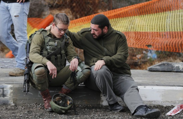 An Isreali soldier is consoled as Israeli forces and forensic experts inspect the site of a Palestinian drive-by shooting attack outside the West Bank settlement of Givat Asaf, northeast of Ramallah, on December 13, 2018. - Two Israelis were killed and at least two others were wounded at the bus …