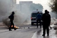 Tunisian policemen stand in a street during a demonstration on December 25, 2018 in the central Tunisian city of Kasserine. - A Tunisian journalist has died after setting himself on fire, officials said, in a protest over harsh living conditions that prompted overnight clashes with police in the country's west. …