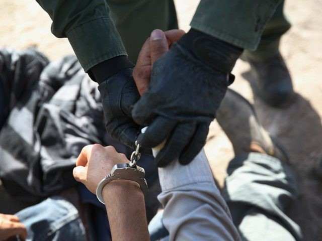 MISSION, TX - APRIL 11: A U.S. Border Patrol agent handcuffs an undocumented immigrant near the U.S.-Mexico border on April 11, 2013 near Mission, Texas. A group of 16 immigrants from Mexico and El Salvador said they crossed the Rio Grande River from Mexico into Texas during the morning hours …