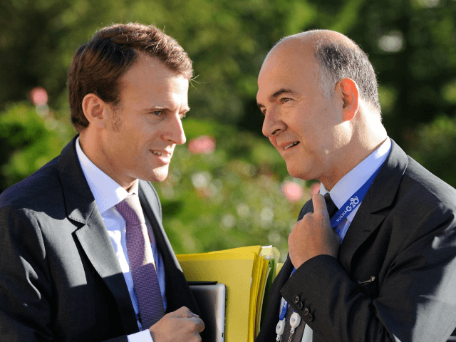 French President's deputy General Secretary Emmanuel Macron (L) and French Economy, Finance and Foreign Trade Minister Pierre Moscovici (R) chat during the G20 summit on September 6, 2013 in Saint Petersburg. AFP PHOTO / JACQUES WITT (Photo credit should read JACQUES WITT/AFP/Getty Images)