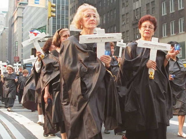"NEW YORK, NY - JULY 13: Cuban Americans dressed in black robes carry crosses as they march down Lexington Avenue in New York 13 July to commemorate the first anniversary of the death of 42 Cubans killed 13 July 1994 on the tugboat ""13 de Marzo"" as they attempted to …"