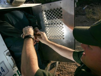 YUMA, AZ - MARCH 17: Handcuffs are removed from a suspected illegal immigrant as he is loaded into the back of a U.S. Customs and Border Protection border patrol vehicle after being apprehended on the California side of the Colorado River on March 17, 2006 near Yuma, Arizona. As Congress …
