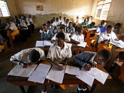 Kampala, UGANDA: Students at St. Denis' Secondary School in Ggaba, a suburb of the capital Kampala, study during the first lesson of the day 23 March 2007. The Ugandan government has recently launched the Universal Secondary Education (USE) programme which enables pupils at certain schools to attend the first year …