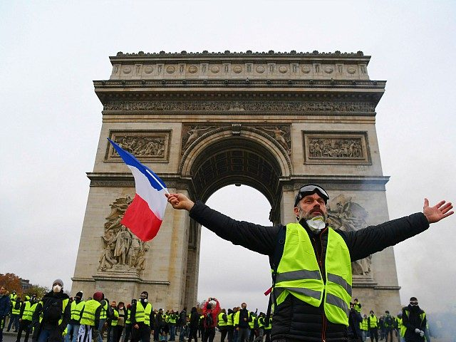 TOPSHOT - A demonstrator waves a French national flag during a protest of Yellow vests (Gilets jaunes) against rising oil prices and living costs in front of the Arc of Triomphe on the Champs Elysees avenue in Paris, on December 1, 2018. - Thousands of anti-government protesters are expected today …