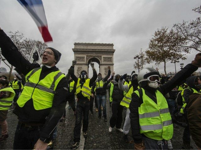 PARIS, FRANCE - DECEMBER 01: Protesters yell during a 'Yellow Vest' demonstration near the Arc de Triomphe on December 1, 2018 in Paris, France. The third 'Yellow Vest' (gilets jaunes) rally in Paris over increased fuel taxes and leadership in the government today caused over 150 arrests in the city …