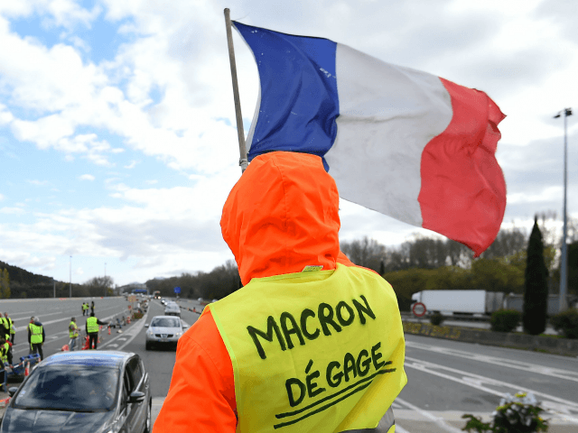 A man with a sign reading 'Macron resign' waves a French flag as 'yellow vests' (Gilets jaunes) protestors gather to protest against rising oil prices and living costs at the highway's toll of La Barque, on December 9, 2018, near Marseille, southern France. - Calls mounted on December 9 for …
