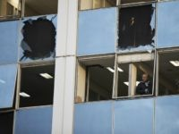 A journalist looks out a broken window after a powerful bomb exploded outside private Greek television station Skai, in Faliro, Athens, on Monday, Dec, 17, 2018. Police said the blast occurred outside the broadcasters' headquarters near Athens after telephoned warnings prompted authorities to evacuate the building, causing extensive damage but …