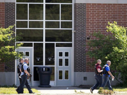 Law enforcement officers walk outside Noblesville West Middle School in Noblesville, Ind., after a shooting on Friday, May 25, 2018. A male student opened fire at the suburban Indianapolis school wounding another student and a teacher before being taken into custody, authorities said. (Robert Scheer/The Indianapolis Star via AP)