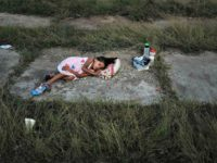 A child sleeps as members of the Central American caravan settle in for the night in an abandoned mot