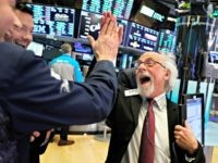 Traders Peter Tuchman, right, slaps a high five before the closing bell on the floor of the New York Stock Exchange, Wednesday, Dec. 26, 2018. The Dow closed up more than 1,000 points in best day for Wall Street in 10 years as stocks rally back from Christmas Eve beating.