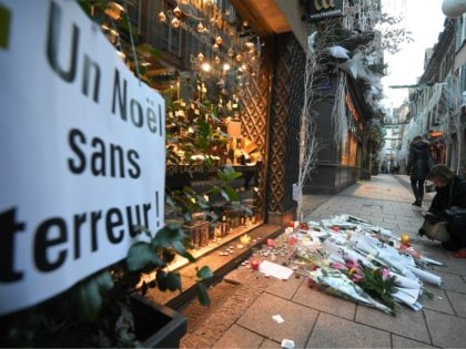 A woman lights a candle in the street next to a message reading 'a Christmas without terror' in tribute to the victims of a deadly shooting two days ago, in central Strasbourg, on December 13, 2018. - Hundreds of French anti-terror police are still hunting for a fugitive gunman who …