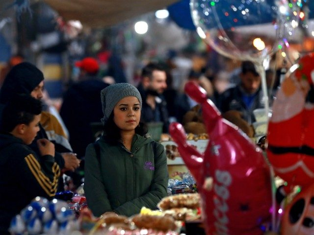 A woman sits next to a peddlar's stall in a market in the northeastern Syrian city of Qamishli on December 12, 2018. (Photo by Delil SOULEIMAN / AFP) (Photo credit should read DELIL SOULEIMAN/AFP/Getty Images)