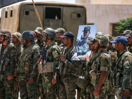 Syrian government soldiers stand holding a picture of Syrian President Bashar al-Assad dressed in a Field Marshal's camouflage fatigues at the Nassib border crossing with Jordan in the southern province of Daraa on July 7, 2018. - Soldiers burned a rebel flag as, together with Russian military police, they took …