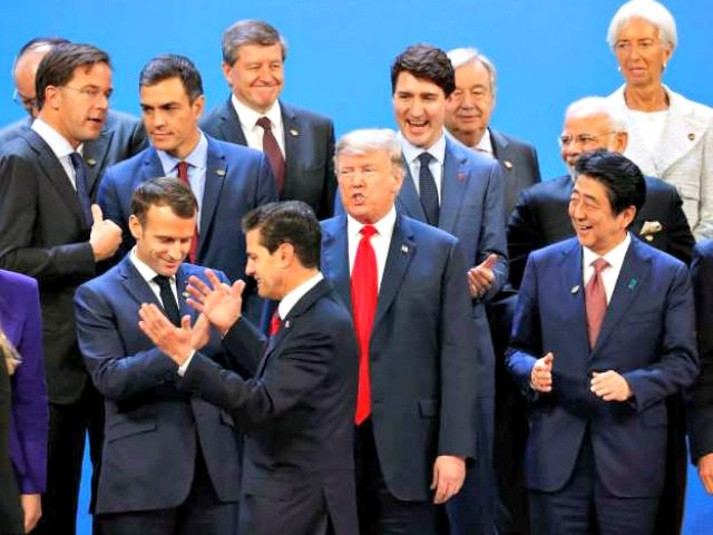 President Donald Trump and other heads of state react to Mexico's President Enrique Pena Neto, throwing his hands up, being the last one to arrive for the family photo at the G20 summit, Friday, Nov. 30, 2018 in Buenos Aires, Argentina.