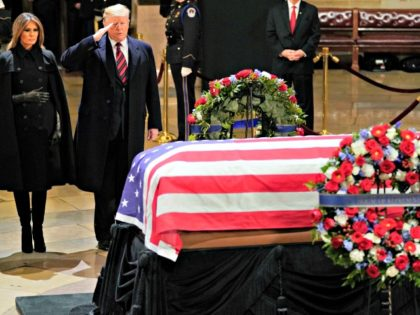 President Donald Trump salutes alongside first lady Melania Trump in front of the flag-draped casket of former President George H.W. Bush in the Capitol Rotunda in Washington, Monday, Dec. 3, 2018.