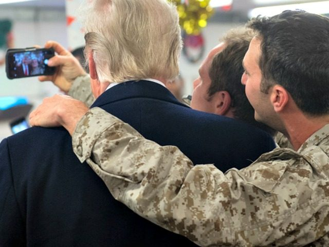 TOPSHOT - US President Donald Trump greets members of the US military during an unannounced trip to Al Asad Air Base in Iraq on December 26, 2018. - President Donald Trump arrived in Iraq on his first visit to US troops deployed in a war zone since his election two …