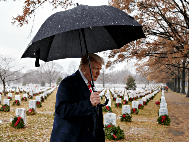 President Donald Trump walks with an umbrella from Section 60 of Arlington National Cemetery in Arlington, Va., Saturday, Dec. 15, 2018, after visiting during Wreaths Across America Day. Wreaths Across America was started in 1992 at Arlington National Cemetery by Maine businessman Morrill Worcester and has expanded to hundreds of …