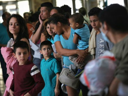 MCALLEN, TX - AUGUST 15: Immigrants stand in line for a bus on August 15, 2016 in McAllen, Texas. Central American immigrant families, who had crossed into Texas through Mexico, are processed at a U.S. Border Patrol center, given temporary legal documents and sent to their destination city, while their …