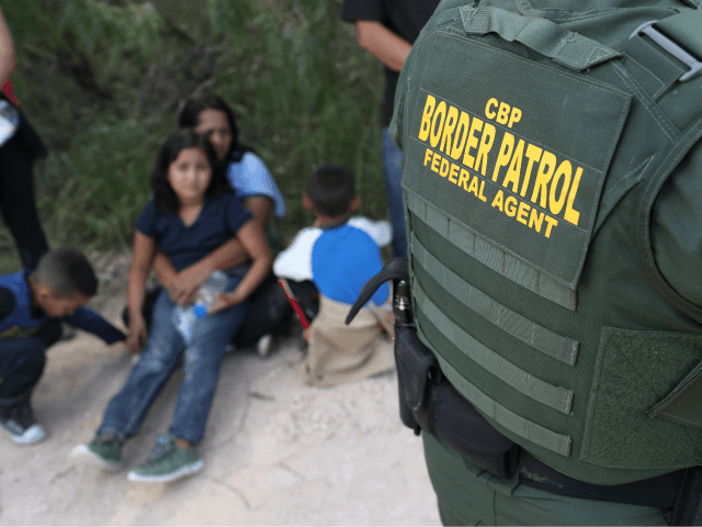Central American asylum seekers wait as U.S. Border Patrol agents take them into custody on June 12, 2018 near McAllen, Texas. The families were then sent to a U.S. Customs and Border Protection (CBP) processing center for possible separation. U.S. border authorities are executing the Trump administration's 'zero tolerance' policy …