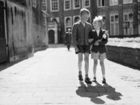 1955: A young boy and girl walking arm-in-arm along the streets of Amsterdam. The girl is holding a carnation. (Photo by Harry Kerr/BIPs/Getty Images)