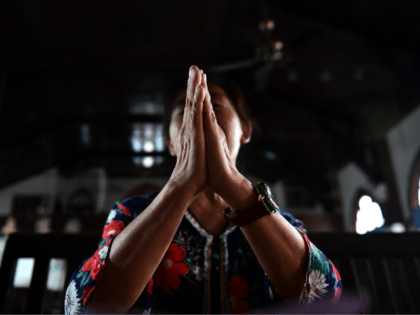 A woman prays inside the Christian Glory church in Wuhan on September 23, 2018. - The landmark deal between China and the Vatican is a win for Beijing, giving official recognition to bishops appointed by the government despite a crackdown on religion, and potentially softening the ground for full diplomatic …