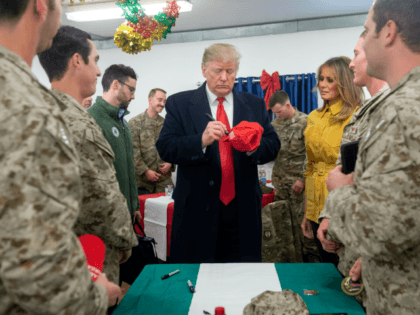 US President Donald Trump signs a hat as First Lady Melania Trump looks on as they greet members of the US military during an unannounced trip to Al Asad Air Base in Iraq on December 26, 2018. - President Donald Trump arrived in Iraq on his first visit to US …