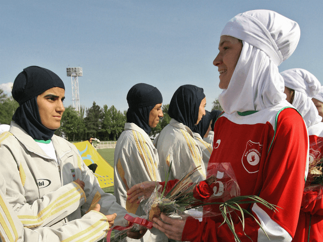 Players from Iran's women national football team (white) exchange flowers with players from Germany's Al-Dersimspor team before a friendly match at Tehran's Ararat stadium 28 April 2006. Hardline President Mahmoud Ahmadinejad announced this week that Iranian women can go to stadiums to watch sporting events, putting an end to a …