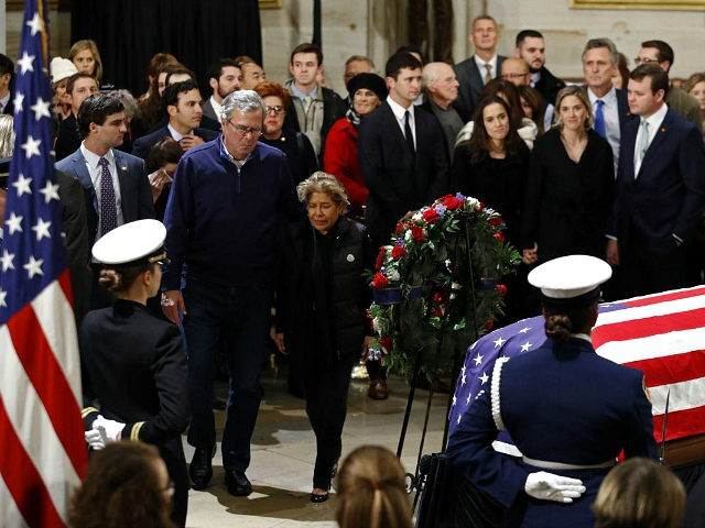 Former Florida Gov. Jeb Bush and his wife Columba approach the flag-draped casket of former President George H.W. Bush as he lies in state in the Capitol's Rotunda in Washington, Tuesday, Dec. 4, 2018. (AP Photo/Patrick Semansky)