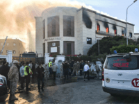 A picture taken on December 25, 2018 shows ambulances, paramedics, and security officers at the scene of an attack outside the Libyan foreign ministry headquarters in the capital Tripoli. - At least one person was killed on December 25 as attackers stormed Libya's foreign ministry after a car bomb exploded …