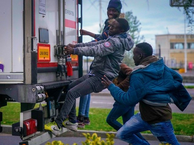 OUISTREHAM, FRANCE - SEPTEMBER 12: Migrants try to board a truck at Ouistreham ferry port in the hope of reaching the UK on September 12, 2018 in Ouistreham, France. After the clamp down at Calais many young migrants are seeking out new routes to the United Kingdom as stowaways on …