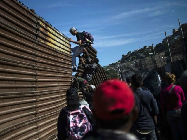 migrants scale border-wall