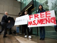 Robert Long (L) and Ada Yu hold signs in favor of Huawei Technologies Chief Financial Officer Meng Wanzhou outside her bail hearing at British Columbia Superior Courts following her December 1 arrest in Canada for extradition to the US, in Vancouver, British Columbia on December 11, 2018. (Photo by Jason …