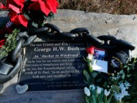 lowers and mementoes lay near a plaque honoring former President George H. W. Bush at a makeshift memorial across from Walker's Point, the Bush's summer home, Saturday, Dec. 1, 2018, in Kennebunkport, Maine. Bush died at the age of 94 on Friday, about eight months after the death of his …