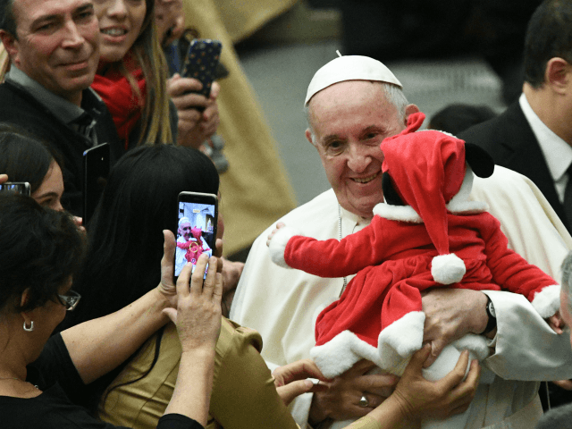 TOPSHOT - Pope Francis holds a baby and poses for photos during an audience for children and families of the Santa Marta dispensary on December 16, 2018 at the Vatican. (Photo by Vincenzo PINTO / AFP) (Photo credit should read VINCENZO PINTO/AFP/Getty Images)