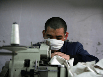 An inmate works on a sewing machine at a prison on March 7, 2008 in Chongqing Municipality, China. There are nearly 5,000 inmates in the prison. China is working to improve education in prisons and help prisoners return to society as law-abiding citizens, with measures to better protect the legitimate …
