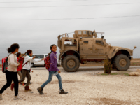 School chikldren walk past a US military vehicle in the Kurdish-held town of Al-Darbasiyah in northeastern Syria bordering Turkey on November 4, 2018. - Three armoured vehicles carrying soldiers wearing the US flag on their uniform arrived in the area after renewed tensions between Ankara and Syrian Kurds, a spokesman …