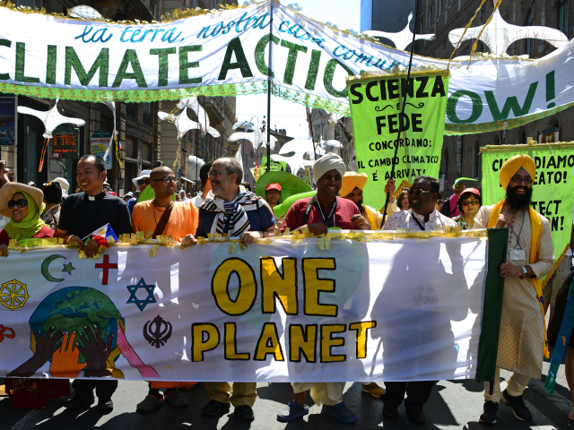 Activists display banners calling for action against world poverty, climate chanege and other environmental issues as they arrive on St. Peter's square prior to Pope Francis's Sunday Angelus prayer on June 28, 2015 at the Vatican. The activists included Christians, Muslims, Jews, Hindus and those of other denominations calling for …